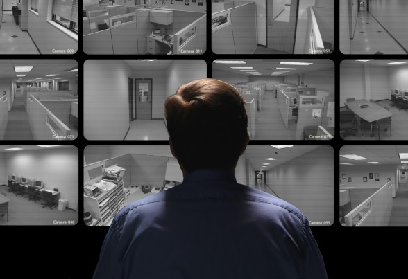 Security guard conducting surveillance by watching several monitors